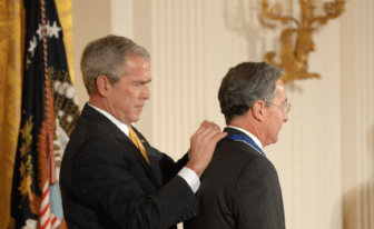 Former U.S. President George W. Bush affixes a medal behind the shoulders of former Colombian President Álvaro Uribe