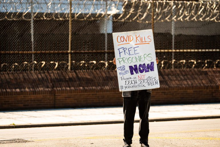 """A person stands in front of a barbed-wire fence outside the Cook County Jail. They are holding a sign, which obscures their face, which reads """"Covid Kills. Free Prisoners Now. Prison is Not a Death Sentence. #JusticeForNick #BLM"""""""