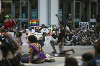 """Protesters sit and kneel in silence for nearly nine minutes in Chicago on Saturday, July 4, 2020, during the """"Boycott 4th of July"""" rally against police brutality."""